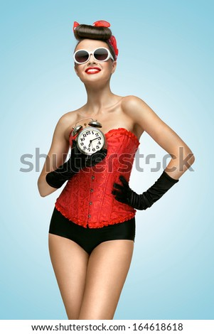 A sexy photo of girl in vintage corset, panties and gloves holding old clock. - stock photo