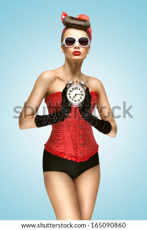 A sexy photo of pin-up girl in vintage corset, panties and gloves holding old clock. - stock photo