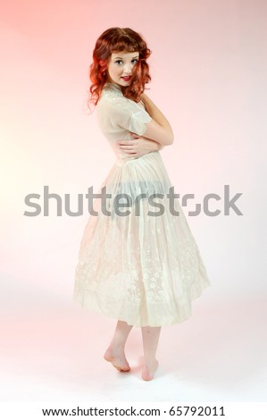 A sexy pin up girl in a sheer white dress. - stock photo