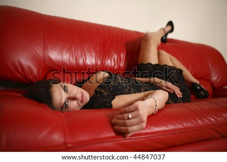 A sexy woman dressed in black on a red couch.
