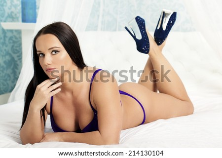A sexy woman wearing lingerie and high heels relaxing on a bed. - stock photo