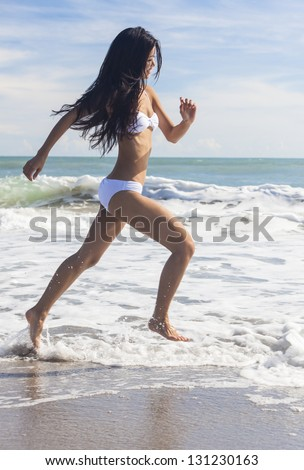 A sexy young brunette Asian woman or girl wearing a white bikini running on a deserted tropical beach with a blue sky