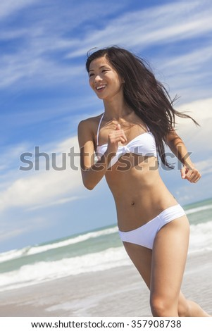 A sexy young brunette Asian woman or girl wearing a white bikini running on a deserted tropical beach with a blue sky  - stock photo