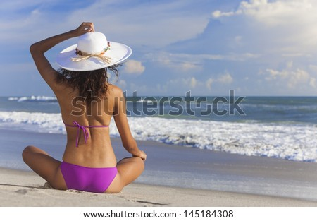 A sexy young brunette woman or girl wearing a bikini and sun hat sitting on a deserted tropical beach with a blue sky  - stock photo