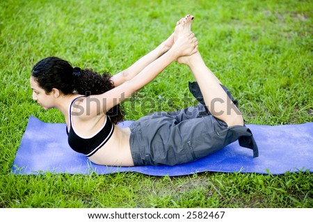 A sexy young hispanic woman in black sports outfit  practices Yoga at the park