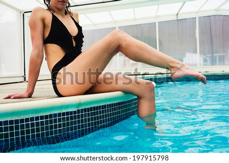 A sexy young woman is relaxing by the edge of a swimming pool - stock photo