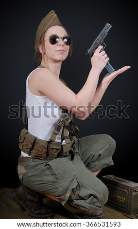 a sexy young woman posing in WW2 military uniform and a weapon