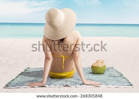 A sexy young woman wearing a yellow bikini sitting on beach - stock photo