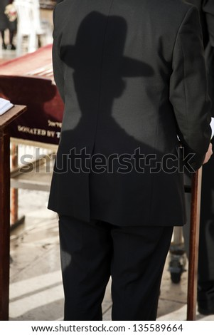 A shadow of an orthodox Jewish man casted on the back side of the suit of the orthodox Jewish man standing in front of him. Shot in the Wailing Wall in the old city of Jerusalem, Israel. - stock photo