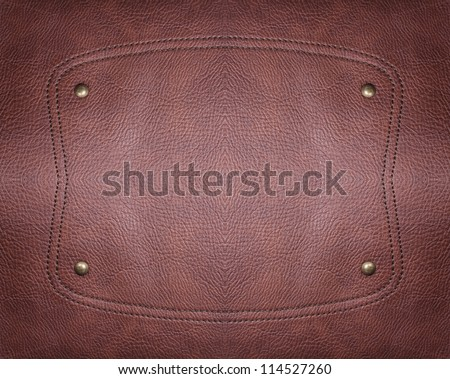 A shape is stitched in a piece of leather with metal studs. - stock photo