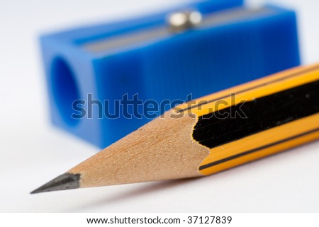 A sharpened pencil on white background, close up version. Very shallow depth of field, focus at the point of the pencil.  A blue pencil sharpener is out of focus at the background.