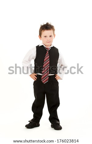 A sharply dressed young boy standing with hands on his hips.