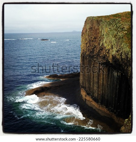 A sheer cliff edge next to the ocean. - stock photo