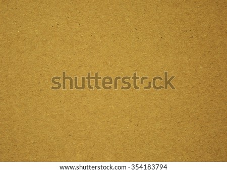 A sheet of brown cardboard with clearly visible texture and fine fibers. Very interesting and interesting background or texture. Close horizontal view.