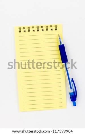 A sheet of lined yellow paper with a blue pen. - stock photo