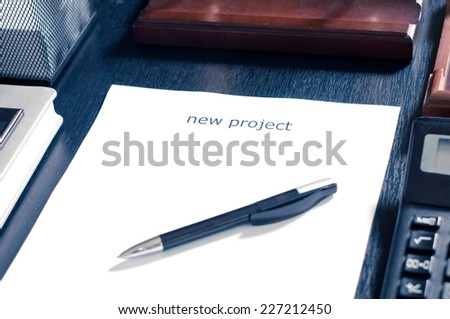 A sheet of paper on the table with the word new project. Insert your text - stock photo