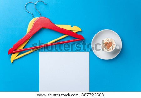 a sheet of the paper, a cup of coffee and two hangers lying on the blue table - stock photo