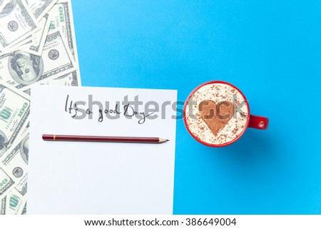 a sheet of the paper, dollars and red cup lying on the blue table - stock photo