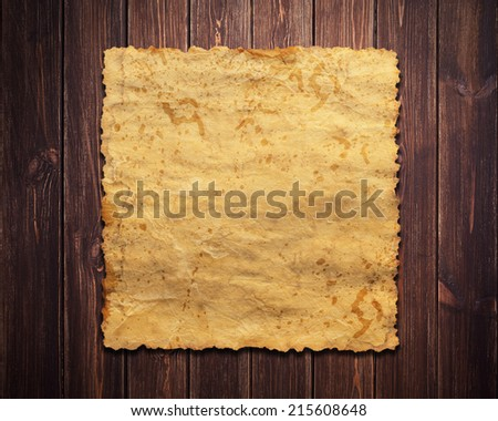 a sheet of vintage paper on wooden background - stock photo