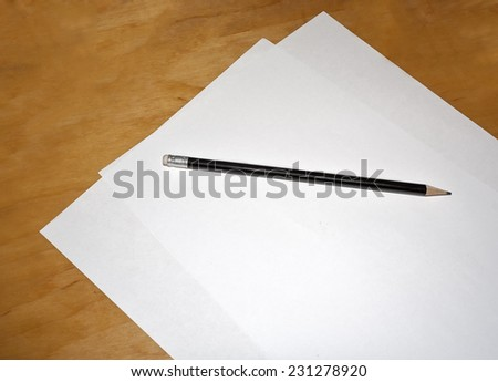 A sheet of white paper and a pencil on the table - stock photo
