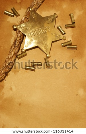 A sheriff badge and gun shells on some antique paper. - stock photo
