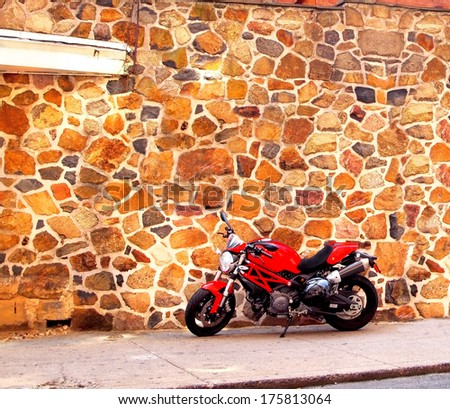 A shiny, fast, red motorcycle is parked in front of an old stone wall in an alley. - stock photo