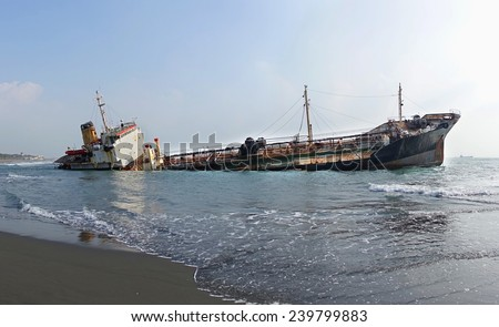 A ship has run aground in shallow waters and is sinking