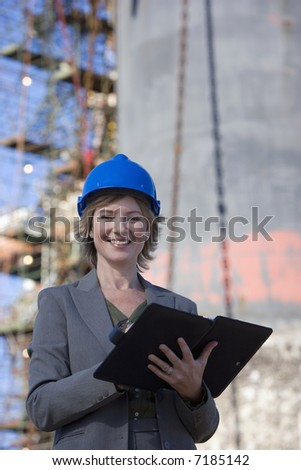 A shipping engineer in front of an oil platform in the harbor