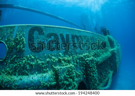 A shipwreck has been intentionally sunk as a diving and snorkeling attraction in Grand Cayman Island. Shipwrecks can serve as artificial reefs, attracting a diverse array of marine life. - stock photo