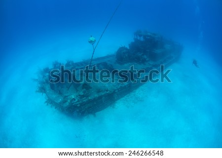 A shipwreck, the Doc Polson, slowly rusts away on a sandy bottom near Grand Cayman in the Caribbean Sea. The wreck acts as an artificial reef. - stock photo