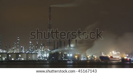 A shipyard by night, nearby an industrial area - stock photo