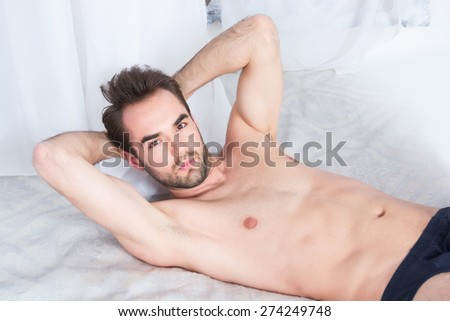 A shirtless young man on a bed - stock photo