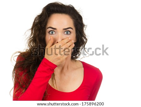 A shocked and frightened woman covering her mouth in surprise and disbelief. Isolated on white. - stock photo