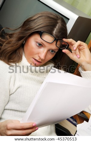 A shocked woman in the office looking at the paper. - stock photo
