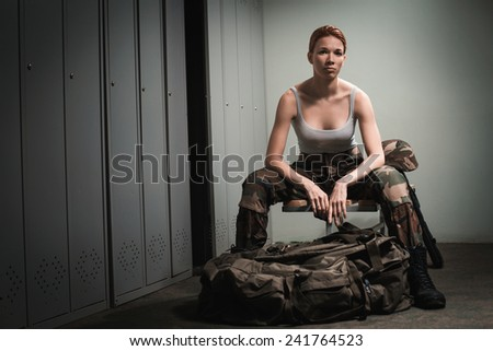 A shoot of young caucasian beautiful redhead woman sitting on the bench at locker room.