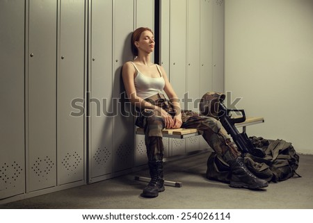 A shoot of young caucasian beautiful redhead woman sitting on the bench at locker room. - stock photo