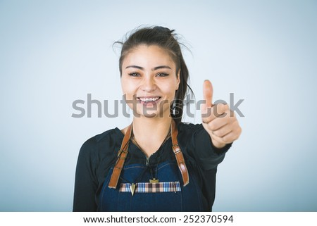 A shoot of young caucasian woman in apron as a barmen. Showing the sign good, thumbs up. - stock photo