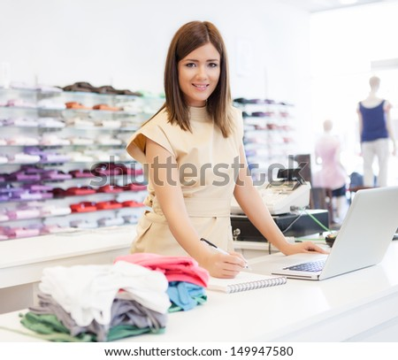 A shop assistant standing at the checkout desk. - stock photo