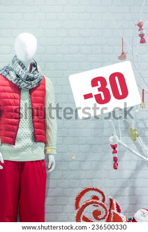 A shop window showing the sale of winter clothing. Discounts on winter clothes. Men's winter clothing. Mannequin in a shop window in winter clothes. - stock photo