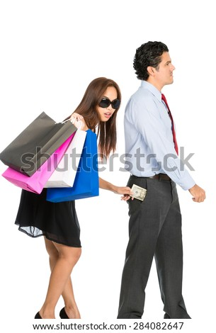 A shopaholic, greedy Asian wife with sunglasses, department store bags, steals money unnoticed from the pants pocket of her husband as he walks away