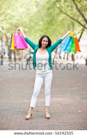 A shopping black woman carrying shopping bags outdoor - stock photo