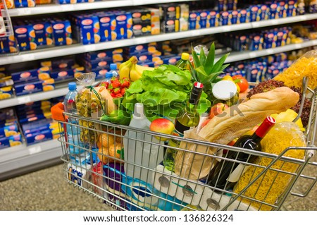 a shopping cart is a transition between the shelves of a supermarket. - stock photo
