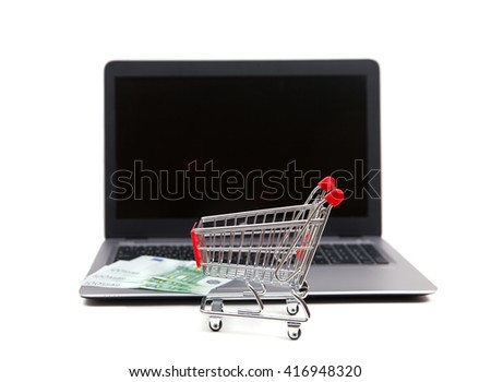 A shopping cart with euro banknotes at notebook