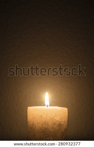 A short candle burns brightly in dark room - portrait interior