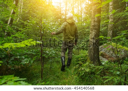 A shot from behind of a man walking through thick forest searching for something like animals maybe mushroom