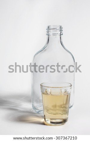 A shot glass and a bottle of Brazilian gold cachaca isolated on white background