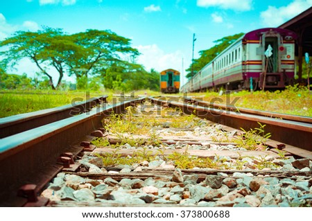A shot looking down the tracks from train platform. Beautiful photo of low speed vintage tro commuter train.train station with a train about to leave. - stock photo