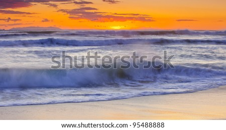 A shot looking out to Catalina Island with a bright orange sunset. - stock photo
