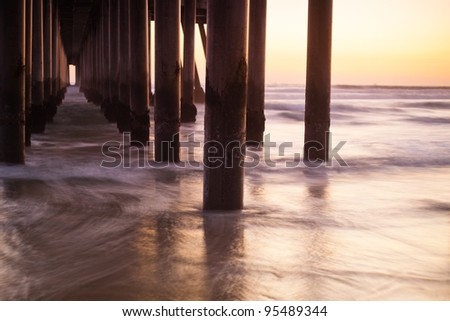 A shot looking out under a pier at all the columns during sunset. - stock photo