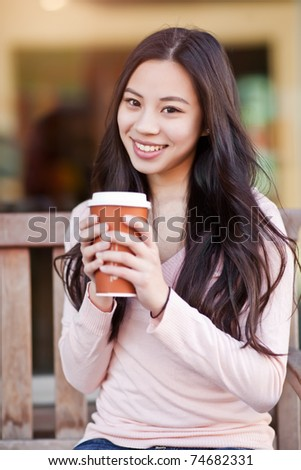 A shot of a beautiful asian woman drinking coffee outdoor